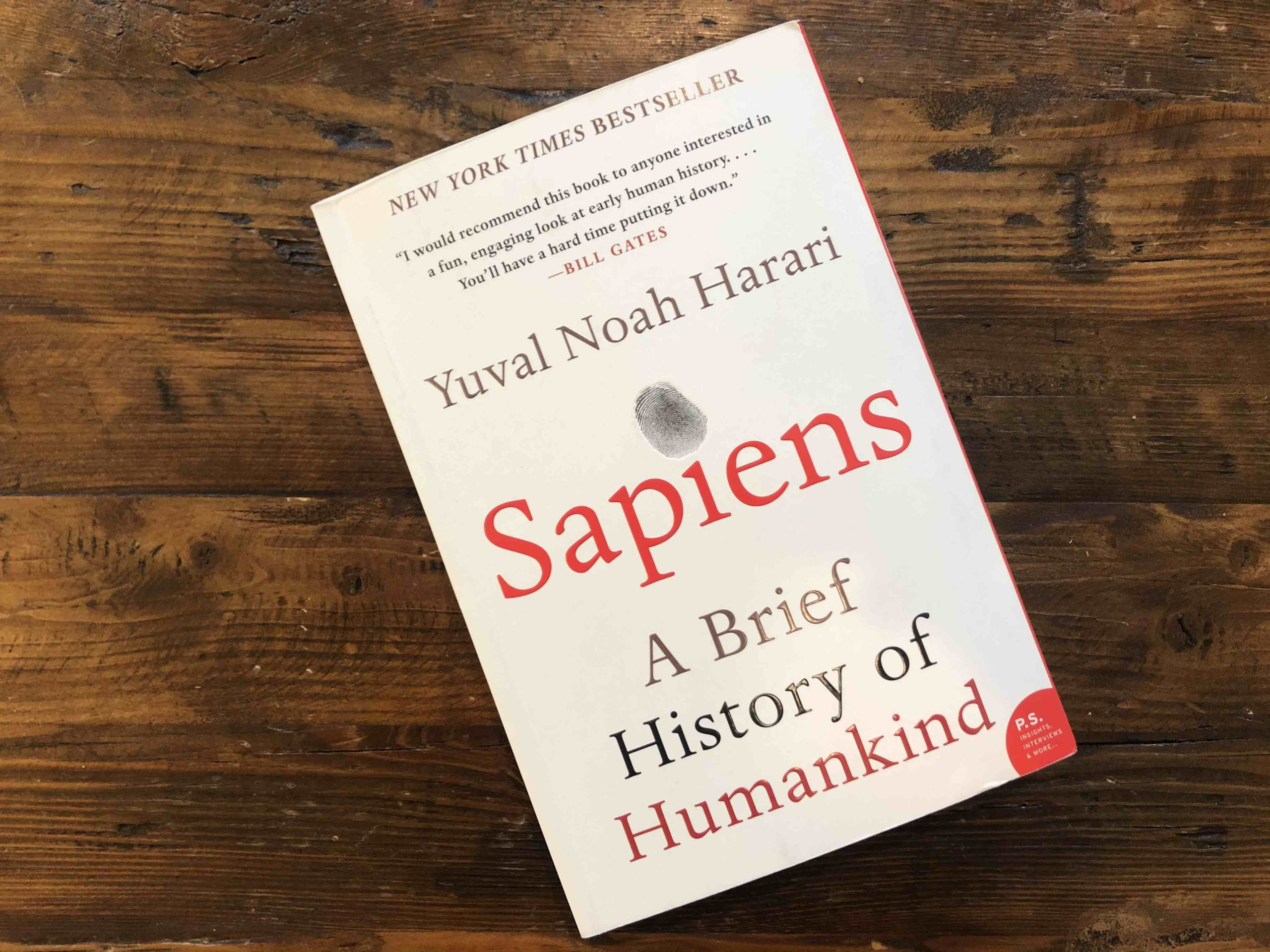 The book Sapiens sitting on a wood coffee table